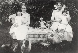 Antique photo of two girls with dolls and a table set for tea